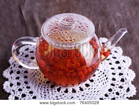 Goji berries drink in glass teapot on lace napkin on wooden background