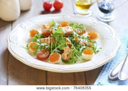 Holiday salad with salmon, quail eggs, cherry tomatoes and red caviar