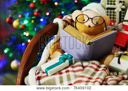 Teddy bear with book and gift boxes in rocking chair on Christmas tree background
