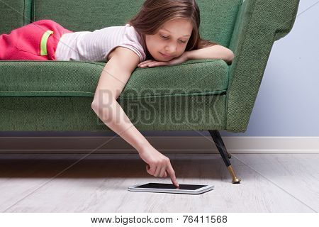 Little Girl Using A Tablet Relaxed On A Sofa