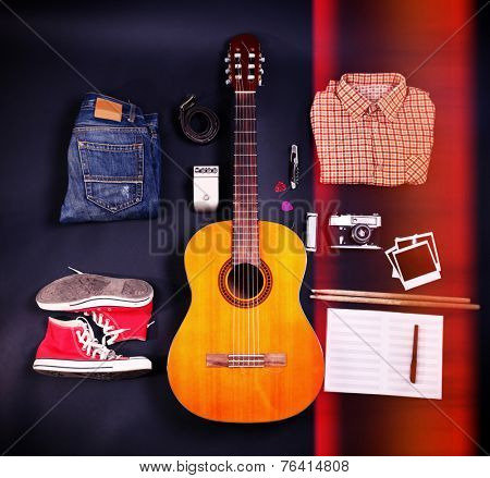 Music equipment, clothes and footwear on black background