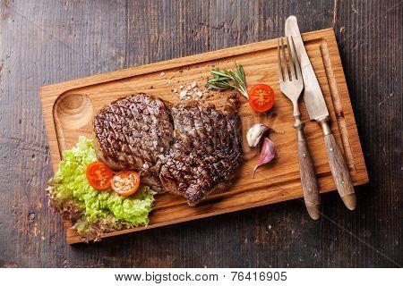 Medium Rare Grilled Beef Steak Ribeye On Cutting Board On Wooden Background