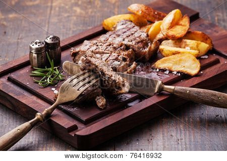 Sliced Well Done Grilled New York Steak With Roasted Potato Wedges On Cutting Board On Dark Wooden B