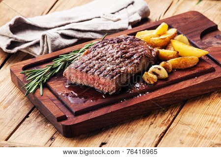 Sliced Medium Rare Grilled Beef Steak Ribeye With Roasted Potato Wedges On Cutting Board On Wooden B