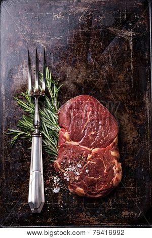 Raw Fresh Meat Ribeye Steak, Rosemary And Vintage Fork On Dark Background