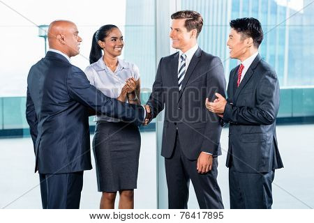 Diversity business team concluding contract with handshake in front of city skyline