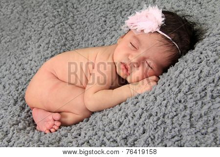 Newborn baby girl of Caucasian and Asian heritage wearing floral head band.