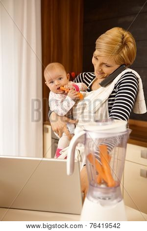 Young mother holding baby, talking on phone, using laptop.
