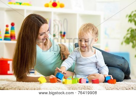 cute mother and her son playing together indoor