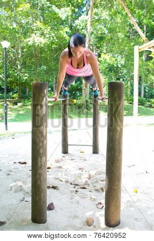 Beautiful woman doing balancing exercise on exercise bar in park