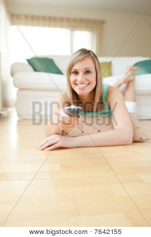 Jolly Young Woman Watching Tv Lying On The Floor