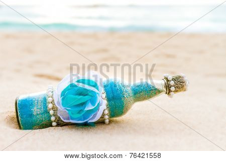 glass bottle with colored sand on natural background, sand ceremony, beach wedding
