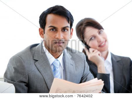 Confident Businessman Reading A Newspaper In A Waiting Room