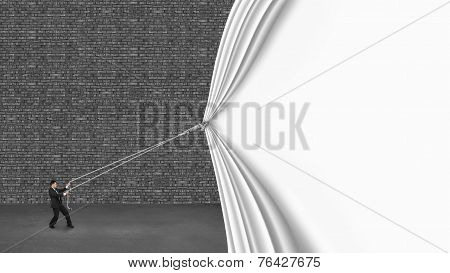 Businessman Pulling Down White Curtain Covering Old Dark Brick Wall