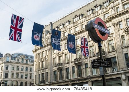 LONDON, UK - SEPTEMBER 27: Union Jack and NFL banners with London Underground sign post. September 27, 2014 in London. Regent street was closed to traffic to host NFL related games and events.