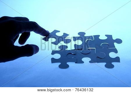 Puzzle with a loose piece touched by a hand