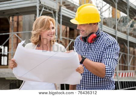 Portrait Of Happy Mature Woman And Male Architect Discussing Plan On Blueprint At Construction Site