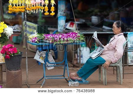 THONG PHA PHUM, THAILAND, JULY 07, 2012: A street flower woman seller is sitting and reading a newspaper in the village of Thong Pha Phum in the Kanchanaburi province, Thailand
