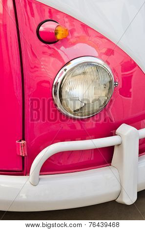 detail of a pink and white classic van headlight and bumper