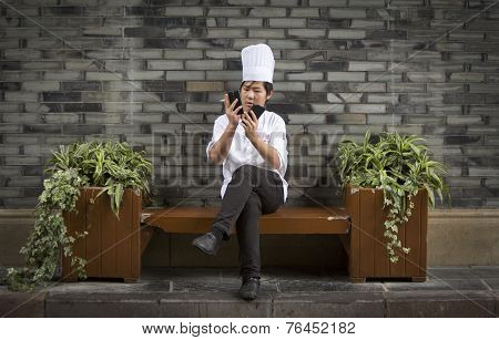 Chinese Cook Checking His Two Phones