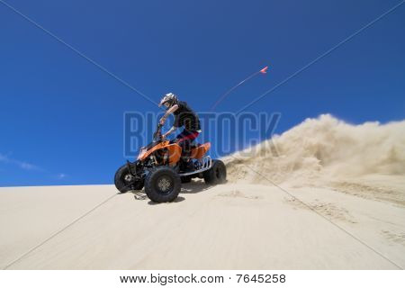 Teen riding ATV in sand dunes