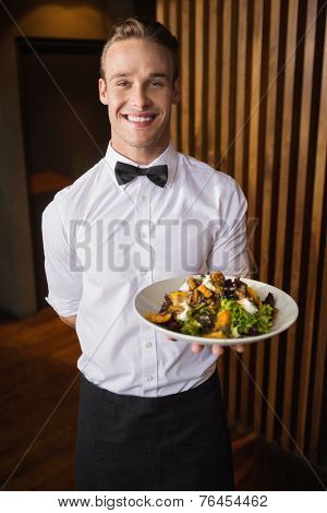 Smiling waiter showing plate of salad to camera in a bar