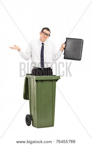 Sad man standing in a trash can and holding a briefcase isolated on white background