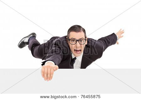 Businessman hanging on the edge of a white panel isolated on white background