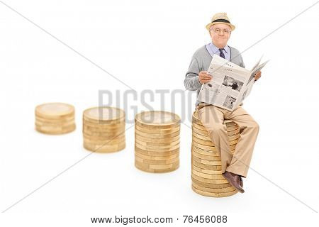 Senior reading the news seated on a pile of coins with the focus on the front pile isolated on white background