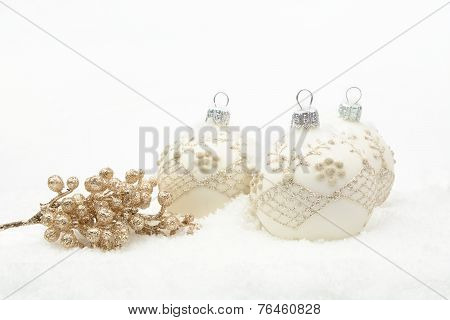Many White Christmas Baubles With Gold Decoration On Snow