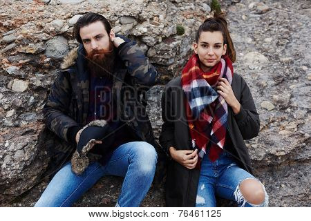 Couple of hikers resting after long way sitting on the rock