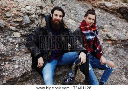 Couple of hipster guys sitting on rock taking break during hike