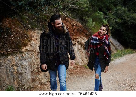 Hikers with backpacks walking on mountain road smiling
