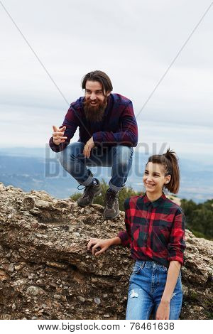 Fashionable hipster man with beard and his charming girlfriend having fun sitting on rock cliff