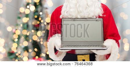 christmas, advertisement, technology, and people concept - close up of santa claus with laptop computer over tree lights background