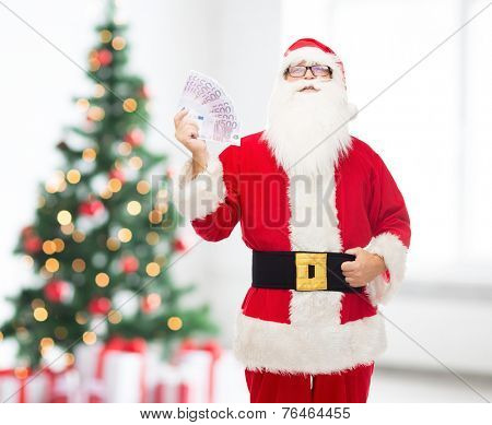 christmas, holidays, winning, currency and people concept - man in costume of santa claus with euro money over living room and tree background