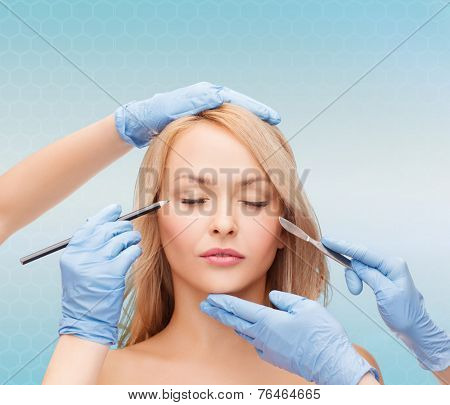 beauty, people and plastic surgery concept - woman face and beautician hands with marker and scalpel