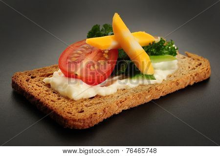 Close-up image of crackers with some cream tomato and cheese