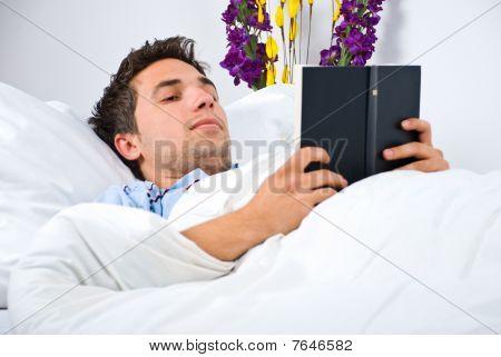 Jovem ler um livro em sua cama