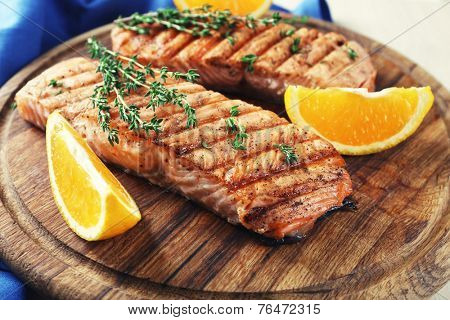 Grilled salmon  and orange slices on cutting board on wooden background