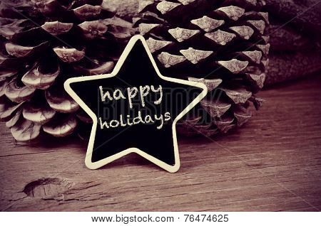 the text happy holidays written in a star-shaped blackboard and some pinecones on a rustic wooden table, in black and white