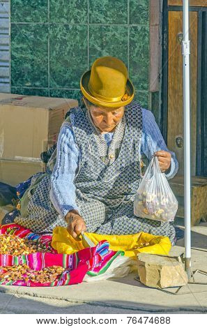 COPACABANA, BOLIVIA, MAY 6, 2014: Local woman in traditional costume and bowler hat sells grilled bean on street