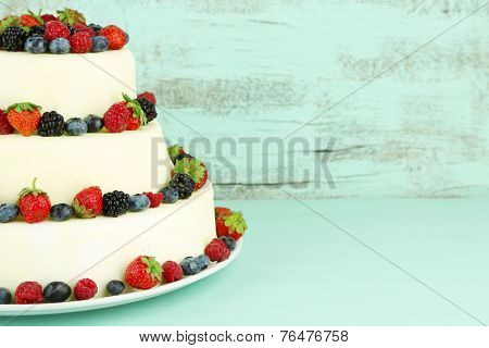 Beautiful wedding cake with berries on color wooden background