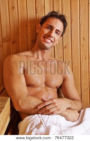 Smiling attractive man sitting in a hotel sauna