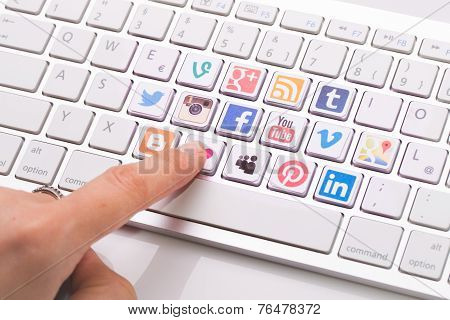 Male Hand Pointing A Social Media Logotype Collection Printed And Placed On White Computer Keyboard.