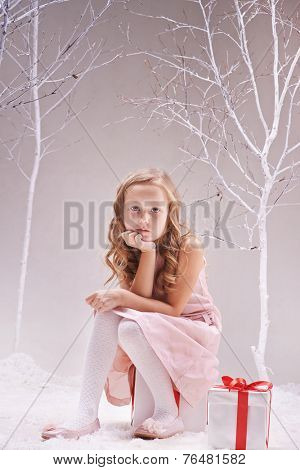 Adorable little girl sitting on giftbox and looking at camera in wonderful forest
