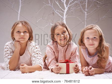 One of three nice girls holding giftbox while they lying on snow in winter garden