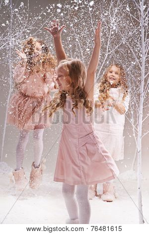 Three little princesses enjoying snow play in amazing winter forest