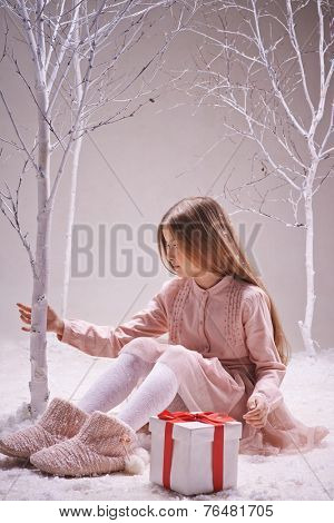Cute girl with giftbox near by sitting in winter forest and touching bare tree trunk