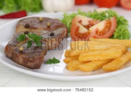 Pork Chop Steak Meat Meal With Fries, Vegetables And Lettuce On Plate